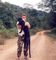 Dr. Lon Grassman holding a collared black leopard in Thailand.